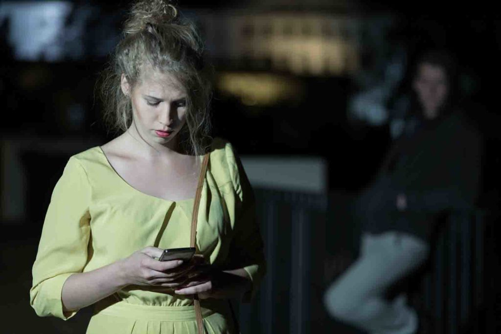 Woman with mobile phone walking alone at night